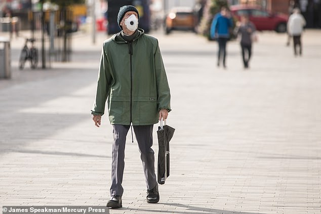 Parts of northern England could be in the midst of a coronavirus endemic, according to leaked Public Health England documents. Pictured: Members of the public wear masks as they walk through Bolton town centre on Tuesday