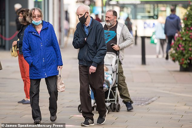 It claims 90 per cent of Greater Manchester boroughs are 'currently experiencing an epidemic phase'. Pictured: People in Bolton this week