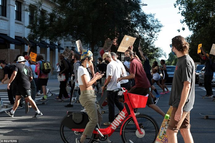 A woman on her bicycle is caught in the middle of an anti-Trump protest held in Washington DC on Saturday