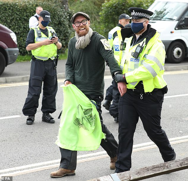 One of the protesters from the bamboo lock-ons is lead away by a police officer outside the Newsprinters printing works at Broxbourne, Hertfordshire