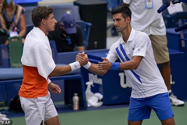 Djokovic shakes hands with Pablo Carreno Busta after defaulting the fourth round match