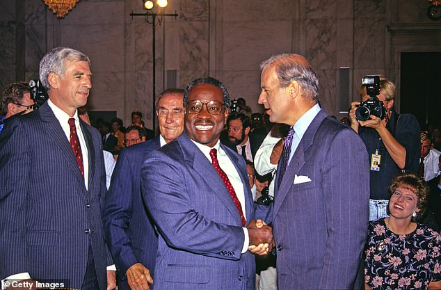 Pictured: Thern- US DC Circuit Court of Appeals Judge Clarence Thomas (center ) shakes hands with then-Chairman of the Senate Judiciary Committee Joseph Biden (right) shake hands prior to a confirmation hearing