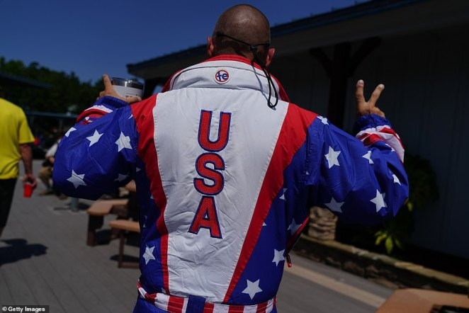 "A man sporting U.S. patriotic garb, with 'USA' written on the back, is shown at a restaurant on Lake Lanier during a ""Great American Boat Parade"""