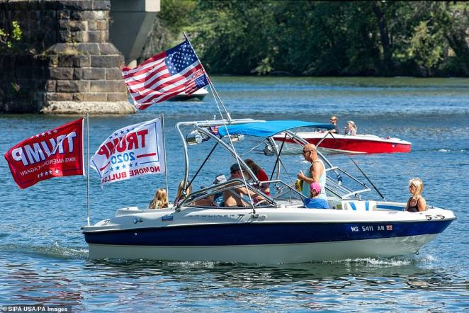 A boat taking part in boat parade for the re-election of President Donald Trump passes the marina at Shikellamy State Park on Lake Augusta near Sunbury, Pennsylvania