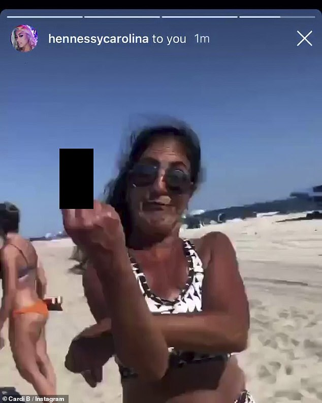 Yikes: The woman flashed her middle finger at Hennessy's camera and then began chanting 'Trump' over and over again