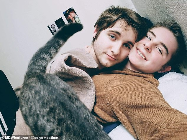 Brandon and Amber discussing the possibility of inviting another person to join their relationship and finally took the plunge when they met Eli at a party. Pictured: Brandon, left, and Eli, right, cuddling with one of their cats