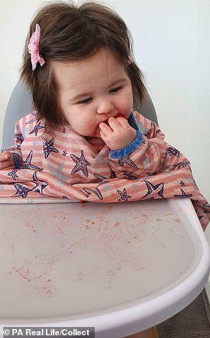 Tayah is pictured in her high chair at eight months old