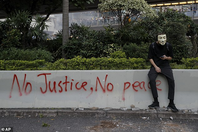 Google updated its Street View Map to include images of the city¿s streets taken last October when Hong Kong was gripped by months of anti-government demonstrations. This file picture shows amasked protester sits near graffiti during a protest in Hong Kong on October 4, 2019