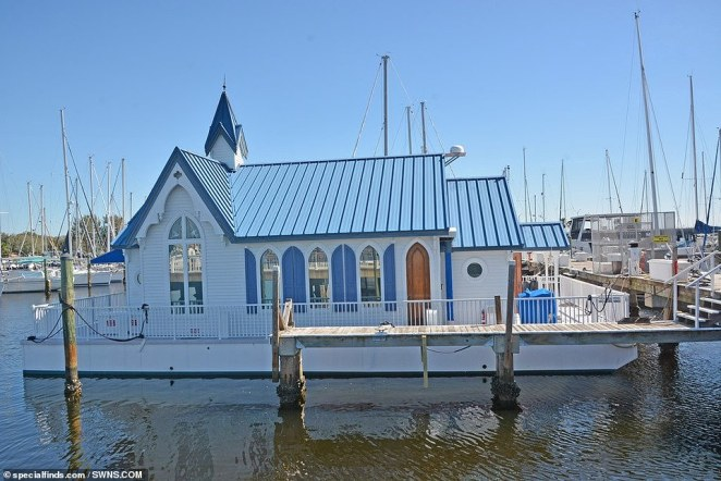 The houseboat, which retains many of its original features including a 30-feet steeple and seven stained-glass windows, has gone on the market for$400,000 (exterior pictured)