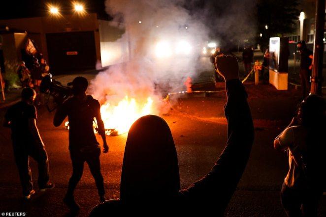 Black Lives Matter protestors chanted 'burn it down' and lit raging fires in the street near a police precinct in Portland (pictured) as they took to the streets on the 101st night of demonstrations in the city