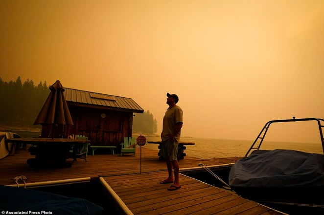 A business owner, who declined to give his name, looks up at the smoke-covered sky from the Creek Fire at his boat rental place on Sunday