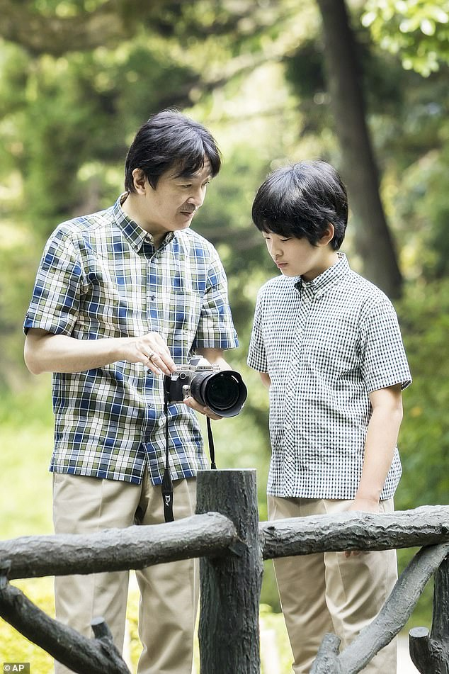 In the sweet pictures, Crown Prince Akishino shows Hisahito how to use his camera in the garden