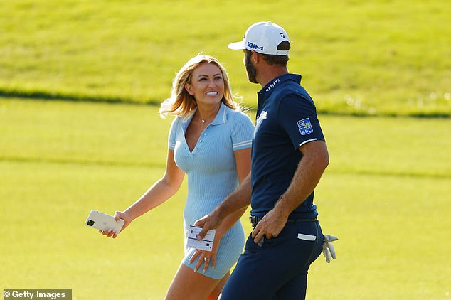 Johnson celebrates with his partner Paulina Gretzky on the 18th green after taking the title
