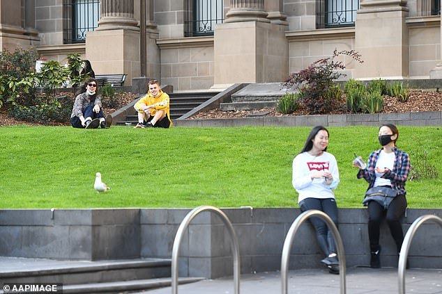 Pictured: People sit on the State Library lawn during Melbourne's Stage Four lockdown on Sunday