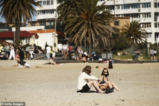 Pictured: Two Melburnians sit on the sand and enjoy the sun at St Kilda Beach on Sunday