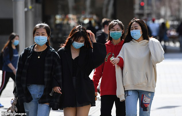 Australia's economy has been hammered by coronavirus restrictions and plunged a record seven per cent the June quarter. Pictured: Melbourne residents wearing masks