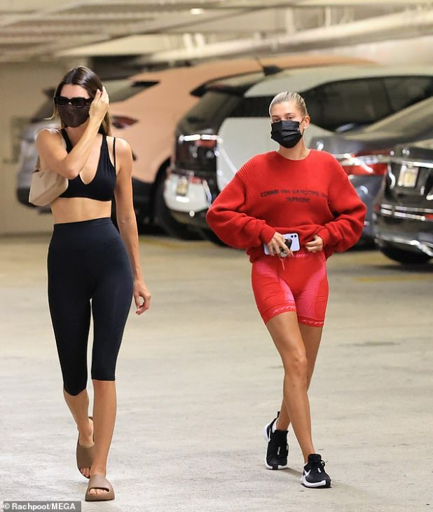 Groceries, but make it fashionable: Kendall was in a black dress to run the wrong way, matching a bralette top with capri leggings, while Hailey was in a red dress