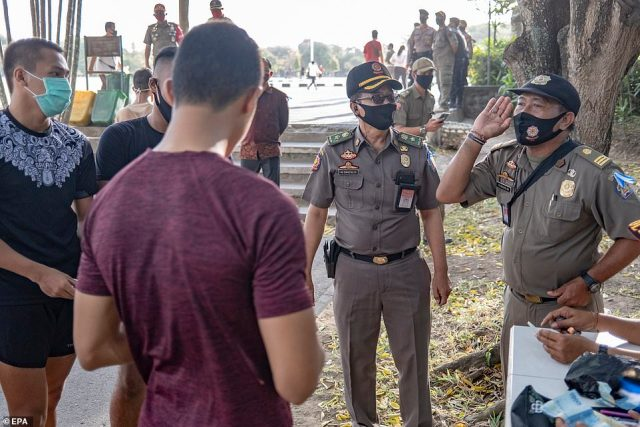 One man is seen being fined 100,000 Rupiah not not wearing a face mask in Denpasar in Bali on Monday