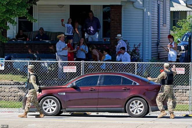 LOUISVILLE, KENTUCKY: Security personnel talk with a crowd that gathered on the porch of a house across from Churchill Downs before the 146th running of the Kentucky Derby on Satursday