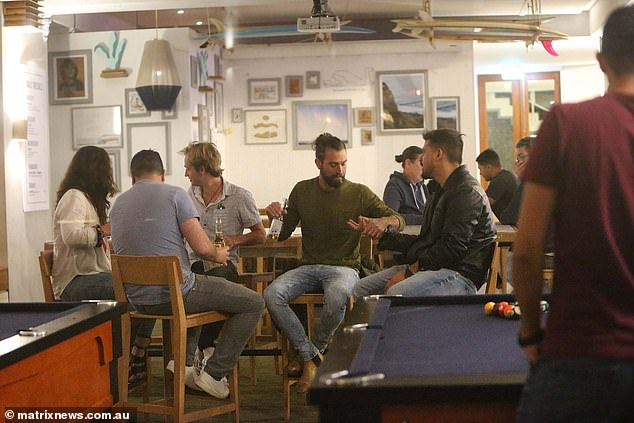 A group of friends enjoy drinks while seated at the Beach Road Hotel in Sydney's Bondi. Sydneysiders can only drink while seated and are banned from standing or dancing