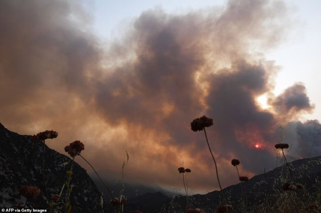 The sun is seen behind smoke from the Bobcat Fire in the Angeles National Forest above Duarte, California, on Monday