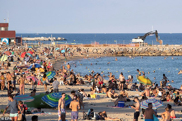 People enjoy a warm afternoon at Sant Sebastian beach, in Barcelona on September 5 after one of the world's toughest lockdowns