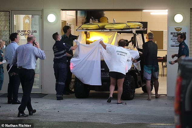 A surfer has been killed by a great white shark at a netted Gold Coast beach in the first attack in the region since 2012. Pictured: members of the public and paramedics covering the man who was treated on the back of a beach buggy
