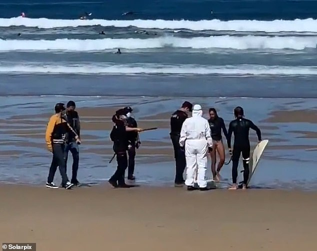The woman was held on suspicion of a crime of disobedience after reportedly ignoring officers who ordered her out of the water for several minutes before heading back to the shoreline