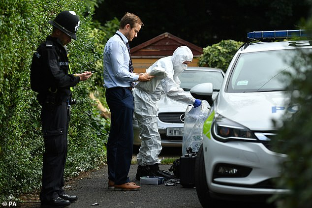 A forensics investigator and police officers outside a property on Nately Grove, Selly Oak, Birmingham, around three miles from the site of the stabbing
