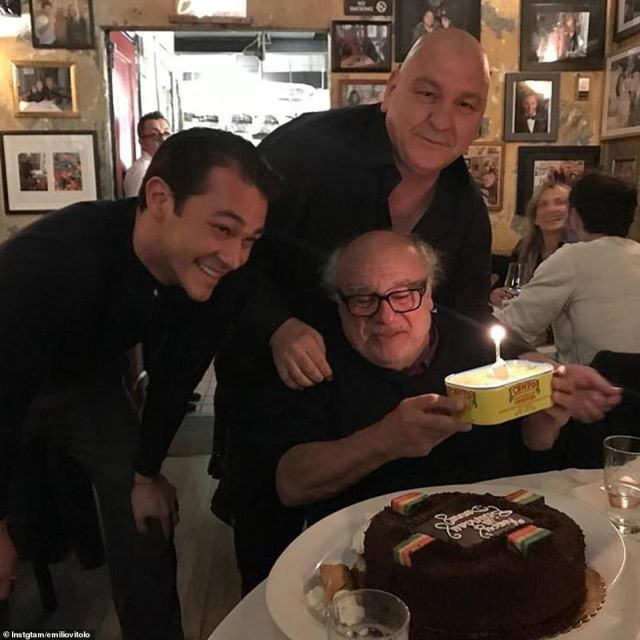 Father and son wishing Danny DeVito a happy birthday during one of the actor's visits to their restaurant