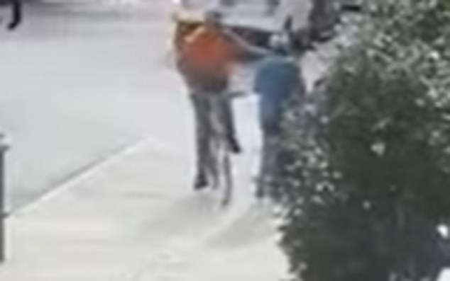 The man is caught on surveillance footage reaching out his left hand and punching the woman