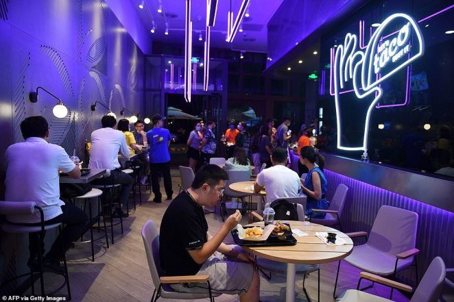 People eat at a newly-opened Taco Bell restaurant in Beijing on August 21, 2020.Restaurants began reopening tentatively in April and since then, there has only been one major spike in infections and deaths which the state says is down to a statistical anomaly and not down to them covering anything up or a second wave.