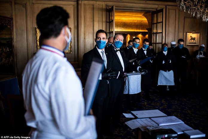 The staff of Paris restaurant La Tour d'Argent is briefed before the lunch service in central Paris on September 2, 2020. France allowed people back into restaurants on June 15 and so far it has had no bearing on COVID-19 deaths