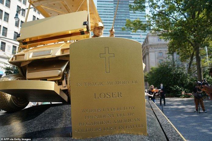 One tombstone reads 'In Tragic Memory Of: 'Loser', referencing claims Trump called US war dead 'losers' and dead Marines 'suckers'