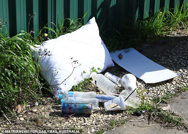 Piles of water bottles, Red Bull and coconut drink were piled up in the home's front yard (pictured) as police examined the crime scene at the weekend