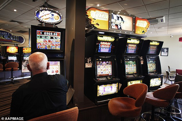 Queensland residents lost$300million on the pokies in July alone, while NSW punters blew $571 million in June while Tasmanians lost$73million in July (man pictured playing a poker machine)