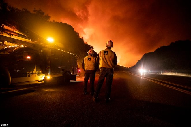 Workers from Pacific Gas & Electric (PGE) watch as the Creek Fire continues to burn on Tuesday