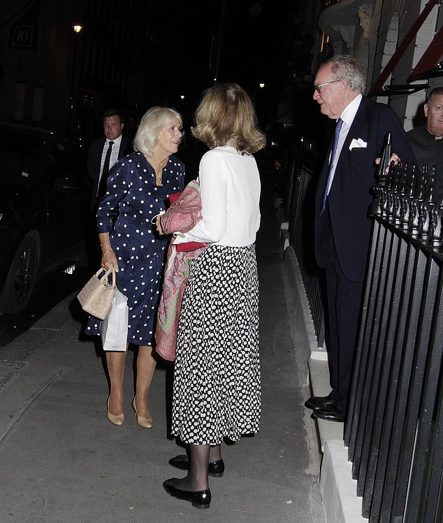 The Duchess of Cornwall was also seen carrying a Toast bag - presumably where she had been shopping earlier in the day. Pictured, speaking with friends
