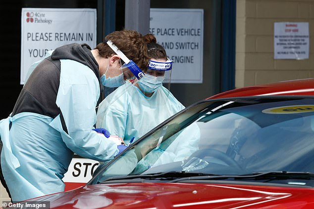 Medical staff perform a coronavirus test on a driver at the Ballarat drive through facility on August 21