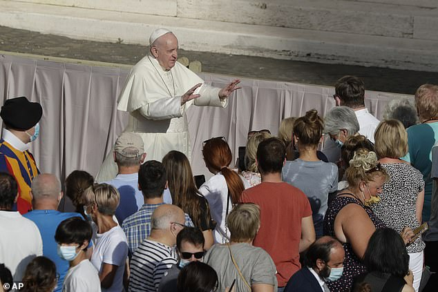 The Pope gestures to the masses at his general audience on Wednesday