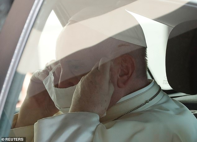 The Pope could be seen putting his mask back on after getting back in the car to leave the ceremony