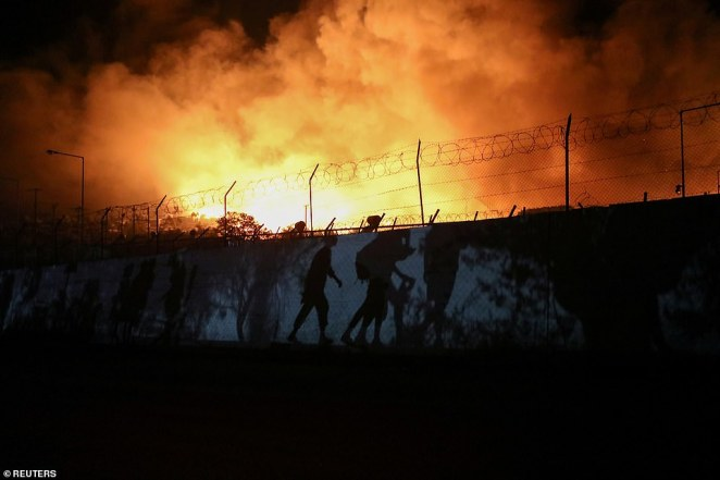 People walk along a perimeter wall on the outskirts of the Moria camp as flames burn in the background after a blaze broke out around 2am Wednesday, September 9