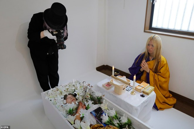 Leiya takes photos of Mako as he plays dead in a coffin during his funeral as a woman, whileLay Kato prays at the side