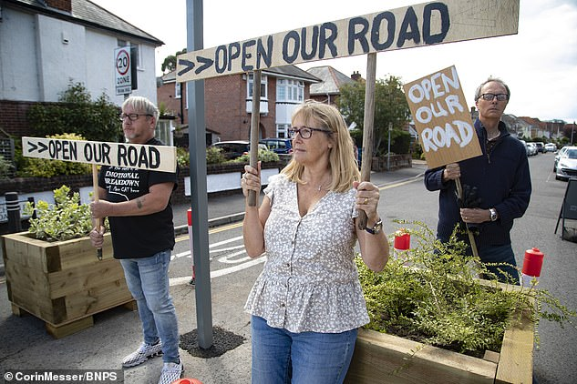The signs, which carried the slogan 'open our road' were put in place by resident Carolyn Hewitt (centre) at the end of Churchfield Road in Poole