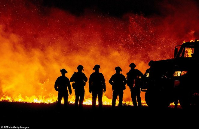 More than 14,000 firefighters are out battling 25 separate blazes in California. Pictured: The Bear Fire in Oroville