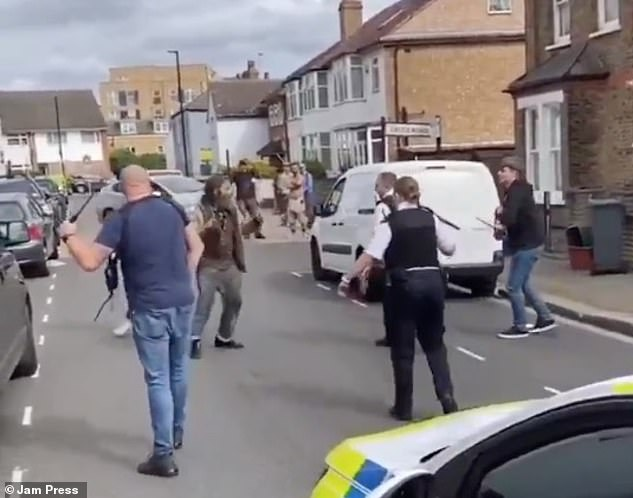 Plain-clothed officers join the two officers at the scene and circle the man on the street