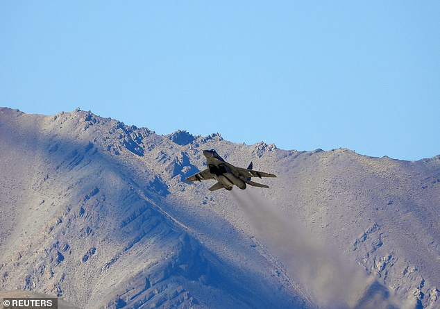 An Indian fighter plane flies over a mountain range in Leh, in the Ladakh region, on Wednesday