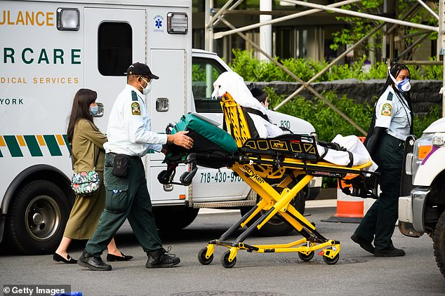 EMS workers wheel a patient outside NYU Langone Health hospital during the coronavirus pandemic hospital on May 24, 2020 in New York City
