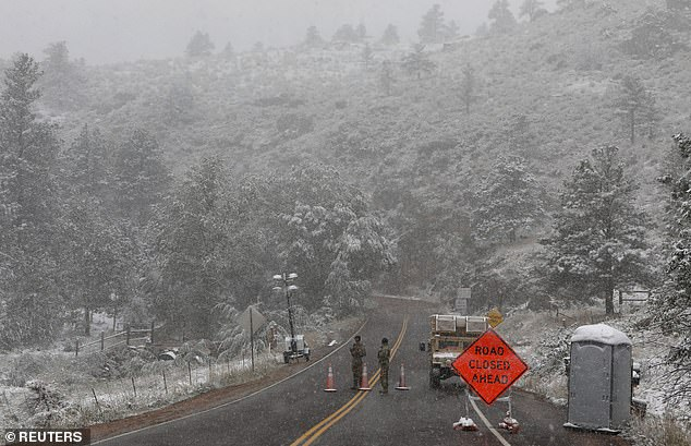 Members of the Colorado National Guard are seen standing in snow on Tuesday, at a roadblock which had been set up for the Cameron Peak wildfire outside of Fort Collins
