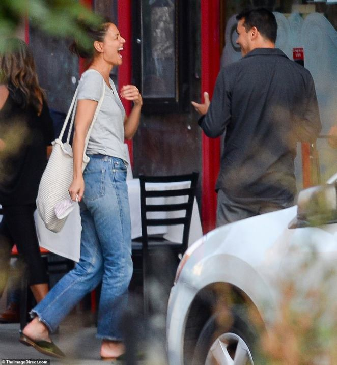 And he makes her laugh! Katie appeared to be laughing at Emilio's joke after kissing him on the street